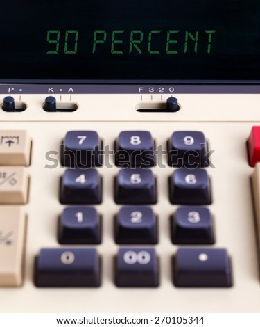 Old calculator with digital display showing a percentage - 90 percent - stock photo