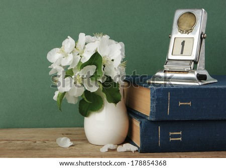 Old calendar and bird cherry branch in a jug on the wooden table - stock photo