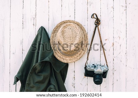 Old camera and clothes hanging on a wall. - stock photo