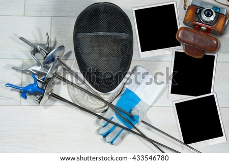 Old camera and empty instant photo frames on a floor with fencing foil equipment - stock photo