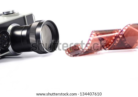 Old camera and  film strip isolated - stock photo