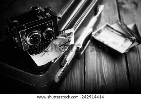 Old camera and old photos are on the case. Black and white.
