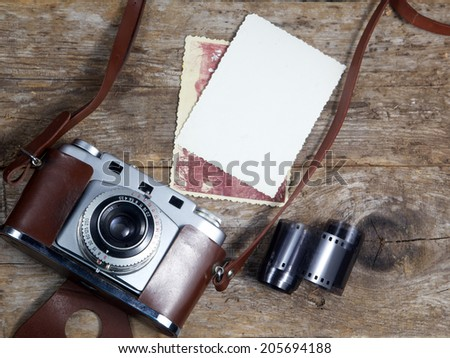 old camera and old pictures  on wooden table, old memories  - stock photo