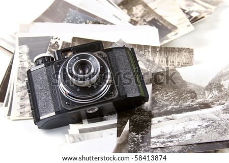 Old camera and pictures on a white background - stock photo
