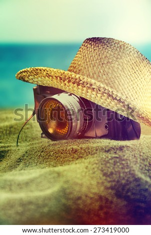 Old camera and sun hat on the beach. - stock photo