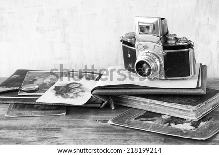 old camera, antique photographes and books over wooden table. black and white photo. - stock photo