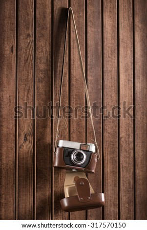 old camera hanging on wooden wall - stock photo