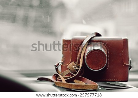 Old camera in leather case - stock photo