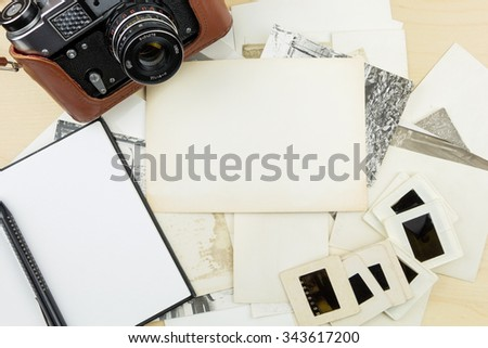 Old camera, notebook and pen on stack of photos and transparency slides - stock photo