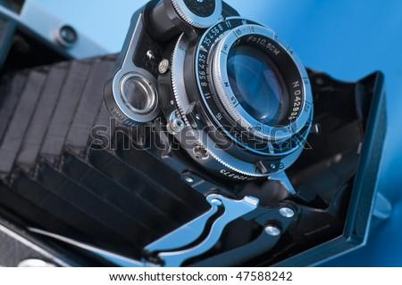 Old camera  on blue background - stock photo
