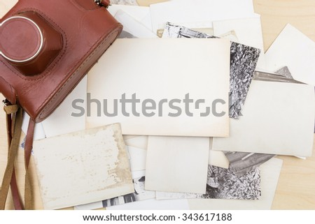 Old camera on stack of photos on wooden surface. - stock photo