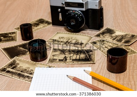 Old camera on the table with notebook, pen, negative film strip - stock photo