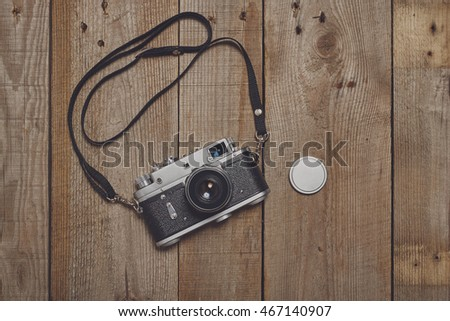 Old camera on vintage wooden background