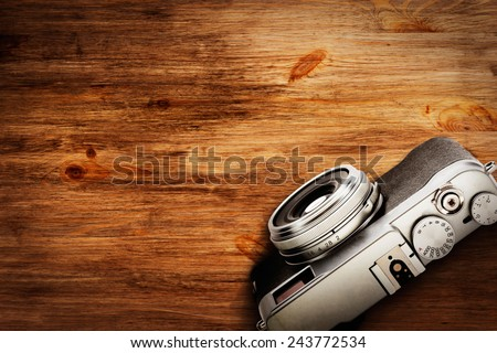 Old camera on wooden desk - stock photo