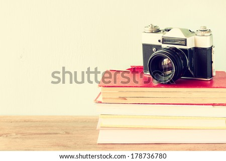 old camera over stack of books. vintage filter. - stock photo