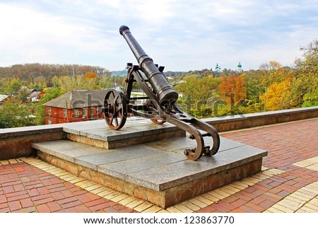 Old cannon in Chernigov and autumn park as background - stock photo