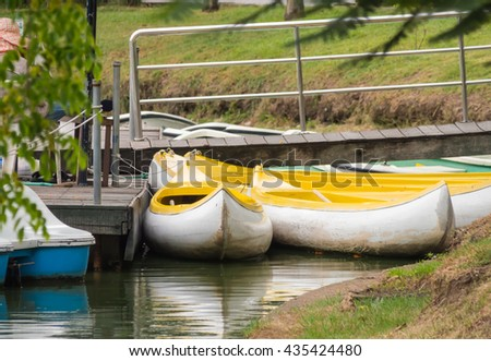 Old canoes on lakeside in city park. - stock photo