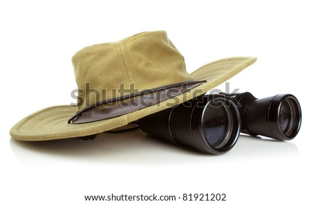 Old canvas hikers hat with a pair of vintage binoculars on white - stock photo