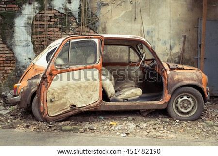 Old car on concrete wall background - stock photo
