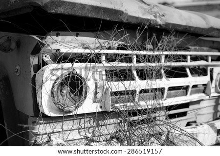 Old car picture, Black and white, limited focus put only on visible right broken light. Vignetting and blur s specially added by around.