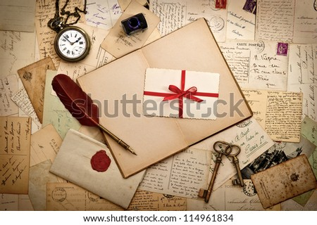 old card with red ribbon over vintage letters and accessories - stock photo