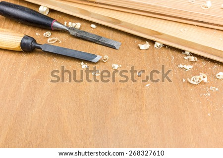 Old carpenter chisel tool with shavings on wooden background - stock photo