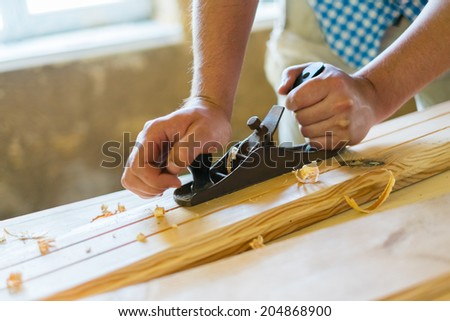 Old carpenter working with wood - stock photo