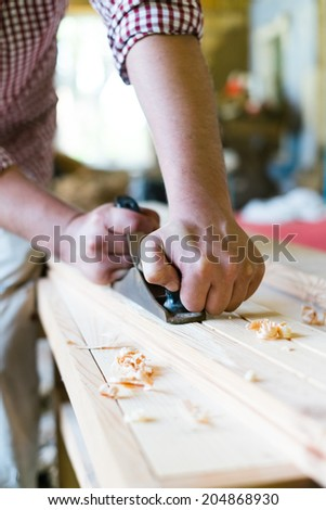 Old carpenter working with wood, retro tinted - stock photo