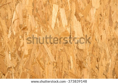 Old carpentery glued solid regular wafer pine flake slices structure layer of sterling smartply aspenite strand fond design. Detail close-up macro view with space for text over hard composite mdf slab - stock photo
