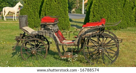 Old carriage left on meadow - stock photo
