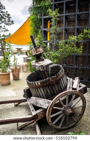 Old carriage with barrel in the green garden