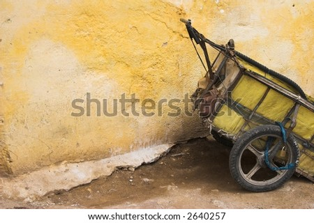 old cart left by wall - stock photo