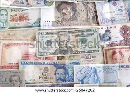 Old cash money from different countries around the world. With a twenty dollar US dollar bill on top. - stock photo