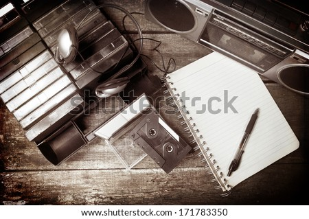 Old cassette tapes, cassette player and blank notebook on wooden surface - stock photo
