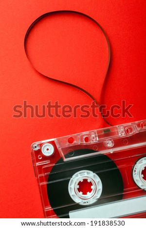 Old Cassette with Tape Unwound on red background - stock photo