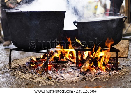 Old cast iron boiling water outside - stock photo