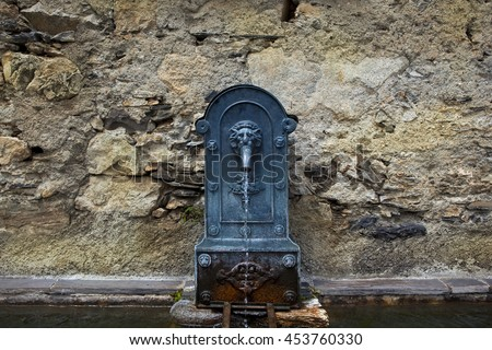 Old cast iron fountain at the wash house of a village in the Pyrenees, France