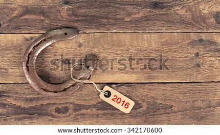 Old cast iron metal Western horse shoeing accessory horseshoe on antique weathered wood plank background - stock photo