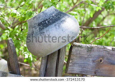 Old cast iron pot hanging on the fence - stock photo