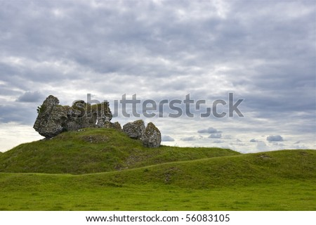 Old Castle in Republic of Ireland against grassy hills and cloud filled sky
