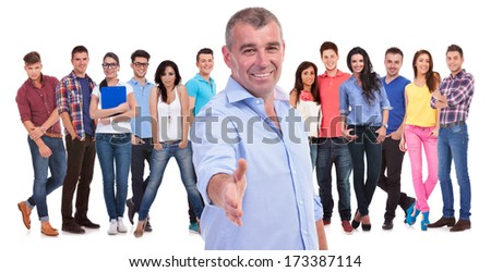 old casual man welcomes you with a handshake to his team of young people on white background