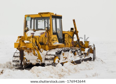 Old caterpillar in a snow field - stock photo