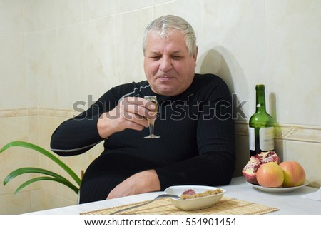 Old caucasian man drinking wine at home