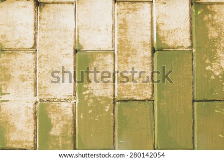 Old cement blocks wall imitation brick wall painted olive color vintage for background. Crack paint looks scare, sad, dirty, formidable. - stock photo