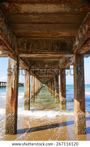 Old cement broken pier at the restless sea. - stock photo
