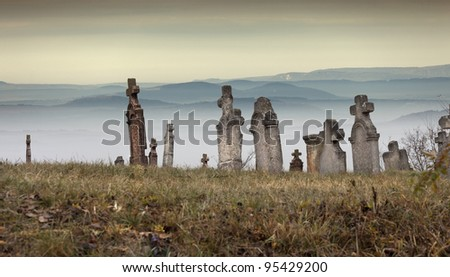 Old cemetery in front of the mountains on a cold, foggy day in Hungary. - stock photo