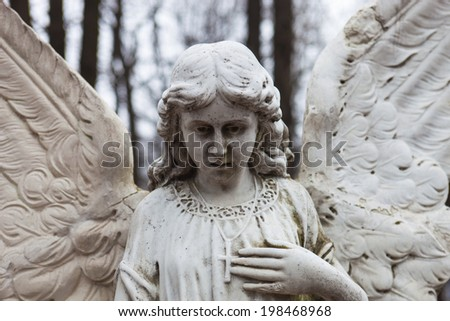 Old cemetery marble sculpture of the angel. - stock photo