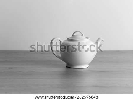old ceramic teapot ,  black and white,old ceramic teapot on a wooden table, black and white, natural light, front photo - stock photo