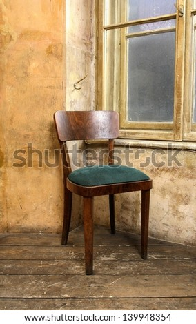 Old chair by the window standing on wooden floor in aged hut