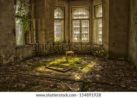 Old chair in an abandoned dilapidated house - stock photo